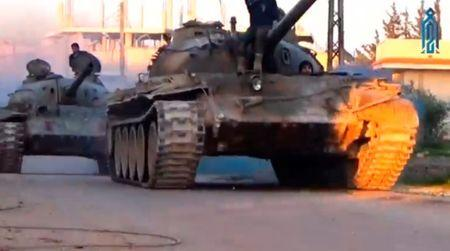 A still image taken from a video uploaded on social media on March 22, 2017, purports to show Tahrir al-Sham rebel fighters on tanks, said to be in Soran district, near Hama