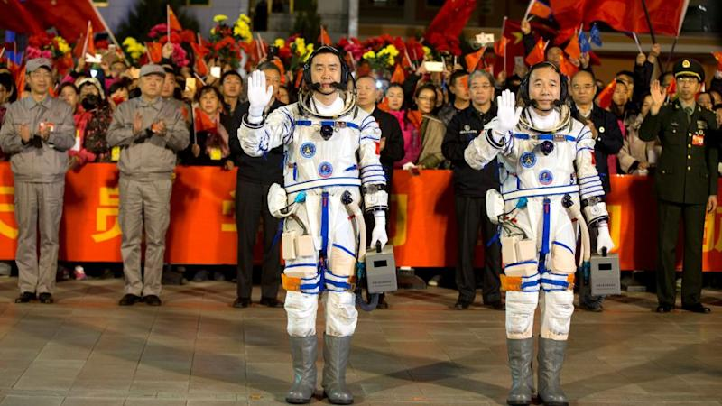 Chinese astronauts Jing Haipeng (R), Chen Dong wave before the launch of Shenzhou-11 manned spacecraft, in Jiuquan, China, October 17, 2016.