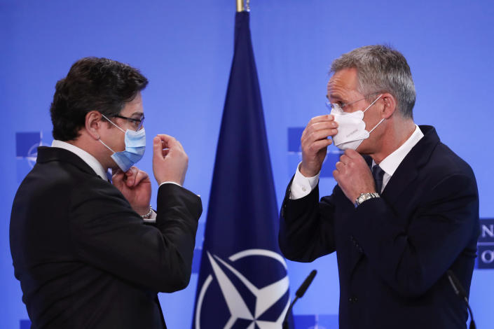 NATO Secretary General Jens Stoltenberg, right, and Ukraine's Foreign Minister Dmytro Kuleba put on their protective face masks after addressing a media conference at NATO headquarters in Brussels, Tuesday, April 13, 2021. NATO Secretary General Jens Stoltenberg and Ukrainian Foreign Minister Dmytro Kuleba met Tuesday to discuss Russia's troop buildup troops along the frontier with Ukraine. (AP Photo/Francisco Seco, Pool)