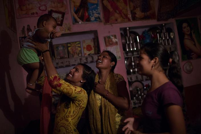 Arti and her sisters play with her son at Arti's family home in Changedi, Udaipur, Rajasthan, India in July 2016. Her sister, on the right (15) got married some years ago, but started spending time with her family-in-law and her husband around seven months ago. The other sister remains unwed for now. (Photo: Rafael Fabrés)