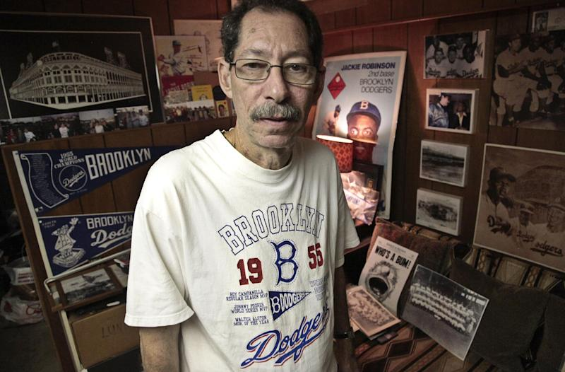 Ron Schweiger, Brooklyn's official borough historian, at his home where he has an extensive Brooklyn Dodgers memorabilia collection on Thursday, Sept. 20, 2012. After decades without a professional sports team following the Dodgers move west, Brooklyn is hitting the major leagues again with a new arena and the Brooklyn Nets' NBA franchise. Schweiger says the new stadium will help replace the sense of loss felt longtime residents for many years after the Dodgers left. (AP Photo/Bebeto Matthews)