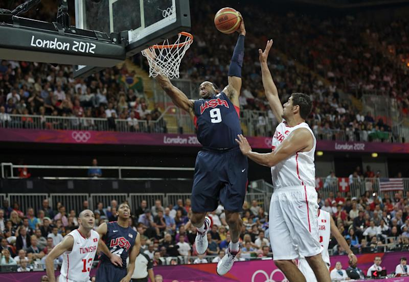USA's Andre Iguodala (9) towers over Tunisia's Mohamed Hadidane as he slam dunks during a men's basketball game at the 2012 Summer Olympics, Tuesday, July 31, 2012, in London. (AP Photo/Charles Krupa)