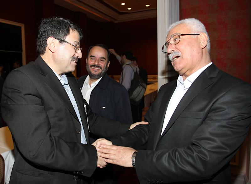 Syrian regime opponent George Sabra, right, shakes hands with Hisham Marwa after winning the election of the Executive Office of the Syrian National Council in Doha, Qatar, Friday, Nov. 9, 2012. (AP Photo/Osama Faisal)