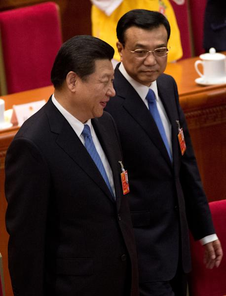 Chinese President Xi Jinping, left, and Premier Li Kiqiang arrive at a plenary session of the National People's Congress at the Great Hall of the People in Beijing Saturday, March 16, 2013. China's new leaders turned Saturday to veteran technocrats with greater international experience to staff a Cabinet charged with overhauling a slowing economy and pursuing a higher global profile for the country without triggering opposition. (AP Photo/Andy Wong)