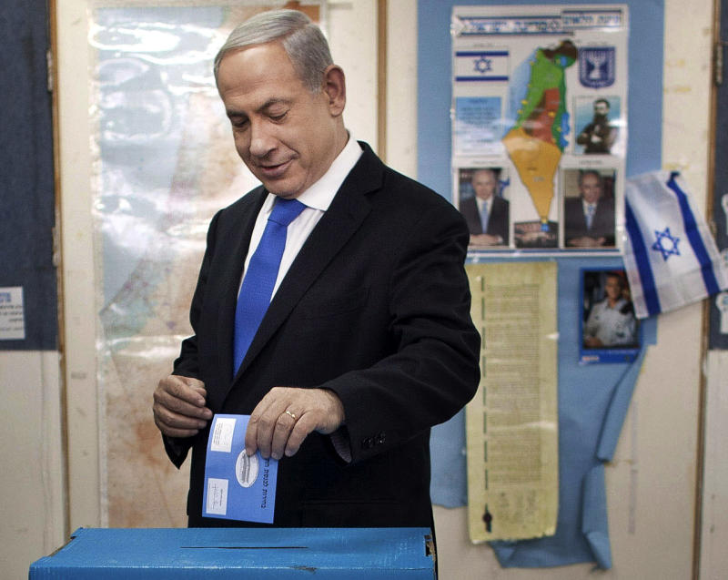Israeli Prime Minister Benjamin Netanyahu casts his ballot together with his wife Sara, left and sons Yair and Avner, background left,  at a polling station in Jerusalem, Tuesday, Jan. 22, 2013. Israelis headed to polling stations Tuesday to cast votes in a parliamentary election expected to return  Netanyahu to office despite years of stalled peacemaking with the Palestinians and mounting economic troubles. (AP Photo/Uriel Sinai, Pool)