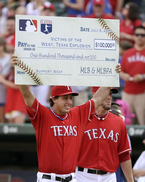 Texas Rangers starting pitcher Derek Holland, left, comes out from the dugout with closer Joe Nathan, right, holding a check from Major League Baseball and the MLB Players Association, before presenting it to West, Texas, city officials during a ceremony before a baseball game Saturday, July 6, 2013, in Arlington, Texas. The Texas Rangers hosted a night to honor residents and first responders from the town devastated by a fertilizer plant explosion. (AP Photo/Tony Gutierrez)