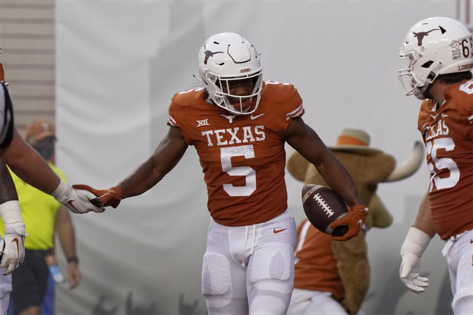 Texas running back Bijan Robinson (5) is congratulated by teammates after a touchdown against Rice during the first half of an NCAA college football game on Saturday, Sept. 18, 2021, in Austin, Texas. (AP Photo/Chuck Burton)