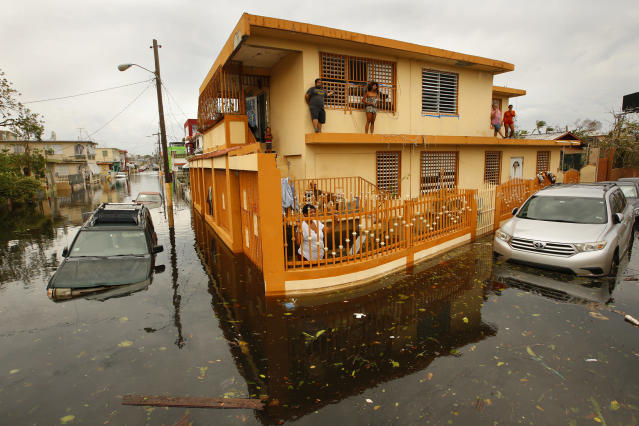 <p>The day after Hurricane Maria made a direct hit on Puerto Rico, residents of Isla Palmeras (translated as Palmeras Island) a neighborhood in San Juan, are surrounded by water on Sept. 21, 2017. (Photo: Carolyn Cole/Los Angeles Times via Getty Images) </p>