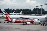 An AirAsia plane (front) arrives at Changi airport terminal in Singapore on December 28, 2014