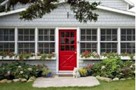 <p>We agree with the pup: the red door against the gray house is the perfect combination and matches the potted flowers, too. </p>