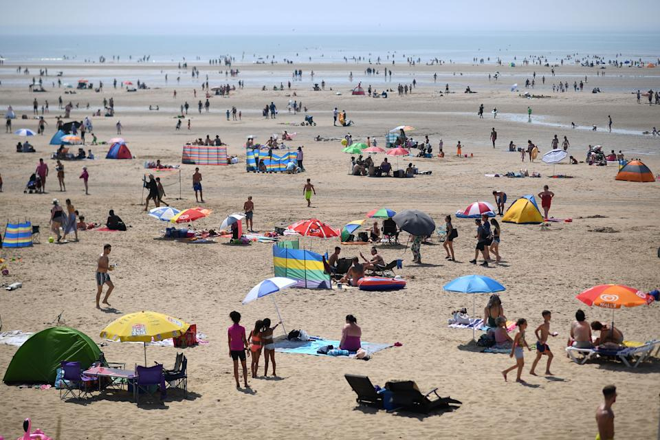 Beach-goers shelter enjoy the sunshine by the sea in Camber Sands, southern England on July 25, 2019, during a heatwave in Britain. (Photo by Ben STANSALL / AFP)        (Photo credit should read BEN STANSALL/AFP/Getty Images)