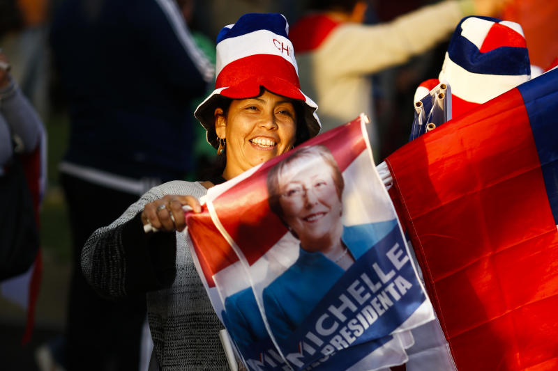 A supporter of Chile's former President Michelle Bachelet celebrates partial election results in Santiago, Chile, Sunday, Nov. 17, 2013. Bachelet is ahead as votes are being counted in Chile's presidential election, but she is running short of the majority needed to avoid a Dec. 15 runoff. (AP Photo/Victor R. Caivano)