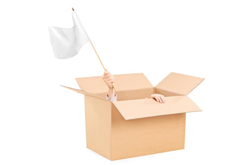A man hiding in a cardboard box waves a white flag.