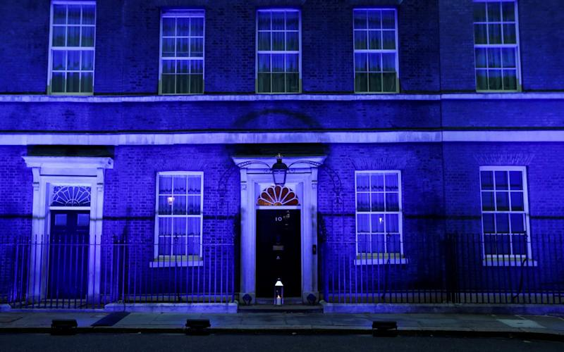A candle lit at the doorstep of 10 Downing Street, illuminated in blue to celebrate the 72nd anniversary of the NHS - REUTERS/Peter Nicholls