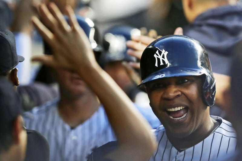 New York Yankees designated hitter Edwin Encarnacion celebrates with teammates in the dugout after hitting a grand slam in the third inning of a baseball game against the Colorado Rockies, Friday, July 19, 2019, in New York. (AP Photo/Kathy Willens)