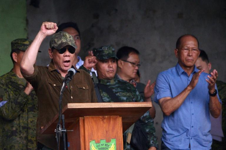 Philippines President Rodrigo Duterte (L) built his electoral success on crowd-pleasing pledges to rid the country of drugs and crime by killing tens of thousands of people