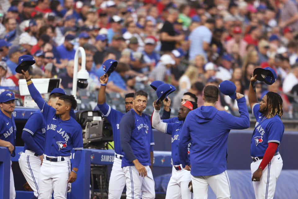 Toronto Blue Jays players raise their hats to fans during the third inning of the team's baseball game against the Boston Red Sox on Wednesday, July 21, 2021, in Buffalo, N.Y. After a road trip, the Blue Jays will begin playing in Toronto for the first time since the COVID-19 pandemic began. (AP Photo/Joshua Bessex)