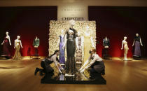 Gallery assistants handle a black and gold sequined 'Oscar' dress worm by Nicole Kidman, amongst other items on display at Christie's, from the archive of fashion designer L'Wren Scott before it is offered at auction, in London, Thursday June 10, 2021. (Jonathan Brady/PA via AP)
