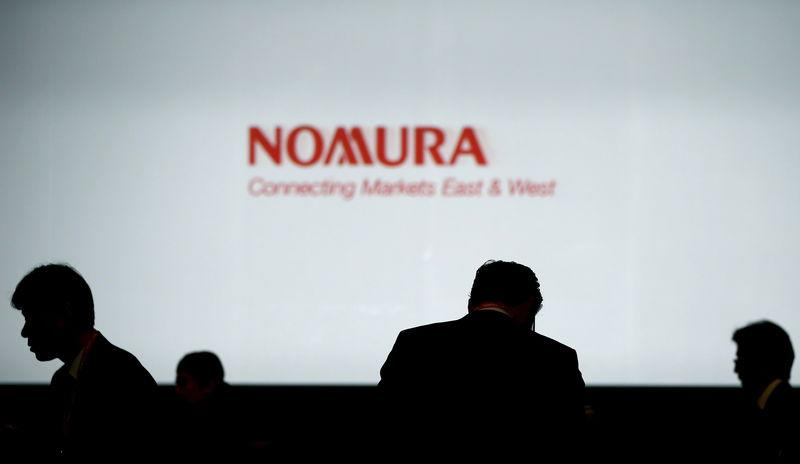 File photo of investors standing in front of a screen showing the logo of Nomura Holdings in Tokyo