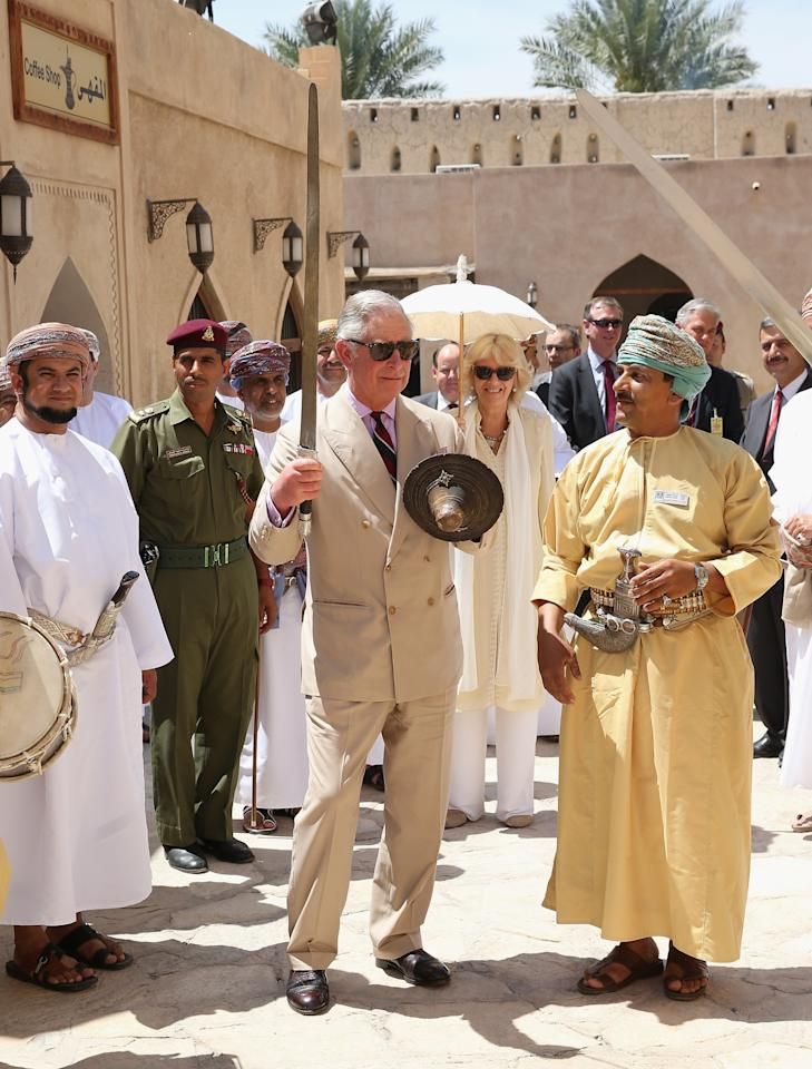 NIZWA, OMAN - MARCH 18:  Prince Charles, Prince of Wales performs a traditional sword dance with local Omanis as Camilla, Duchess of Cornwall look on as they visit Nizwa Fort on the eighth day of a tour of the Middle East on March 18, 2013 in Nizwa, Oman. The Royal couple are on the fourth and final leg of a tour of the Middle East taking in Jordan, Qatar, Saudia Arabia and Oman.  (Photo by Chris Jackson/Getty Images)