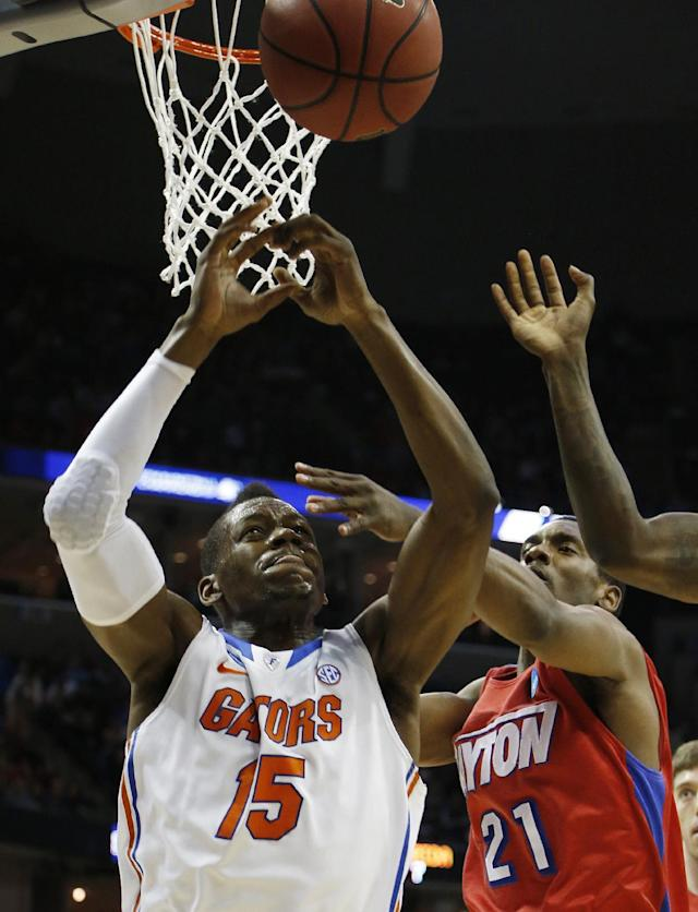 Florida forward Will Yeguete (15) and Dayton forward Dyshawn Pierre (21) vie for a rebound during the first half in a regional final game at the NCAA college basketball tournament, Saturday, March 29, 2014, in Memphis, Tenn. (AP Photo/Mark Humphrey)