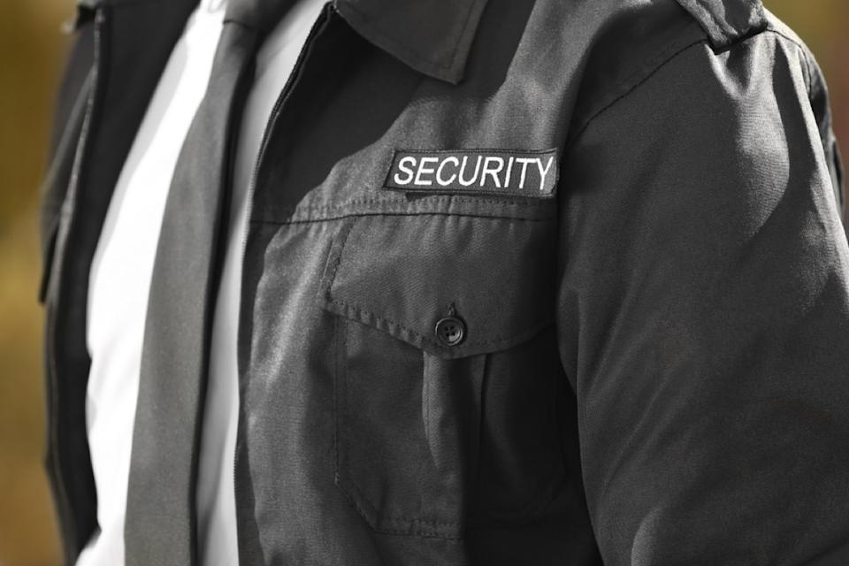 """Closeup of bodyguard's chest with """"Security"""" tag and tie"""