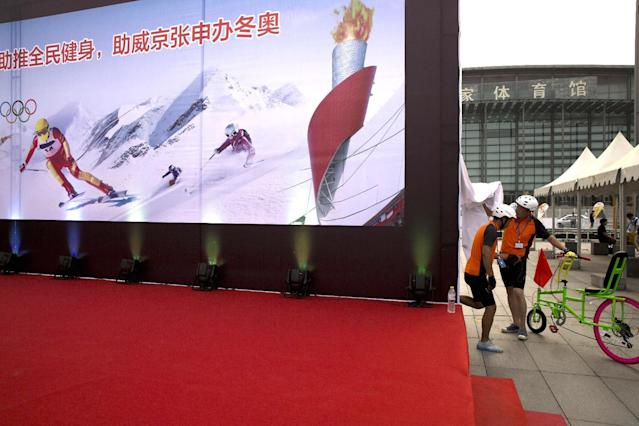 "In this Aug. 8, 2014 photo, cyclists prepare to take part in a carnival near a billboard promoting Beijing's bid for the 2022 Winter Olympics in Beijing. China, the new front-runner to host the 2022 Winter Olympics, doesn't have a long winter sports tradition; in fact, just 20 years ago, there were fewer than 10,000 skiers in the entire country - out of a then-population of 1.2 billion. The words on a board read: ""Promote exercise for everyone, promote Beijing Zhangjiakou bid for the Winter Olympics."" (AP Photo/Ng Han Guan)"