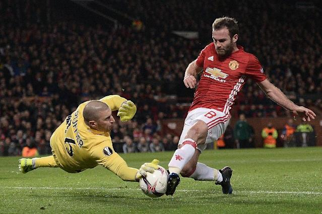 Saint-Etienne's goalkeeper Stephane Ruffier (L) saves the ball as Manchester United's midfielder Juan Mata tries to play a rebounded shot during the UEFA Europa League Round of 32 first-leg football match on February 16, 2017 (AFP Photo/Oli SCARFF )