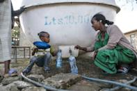 A displaced woman and child collect water from a tank at a school where they are sheltering