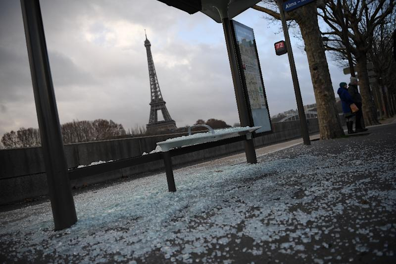 Cleaners swept up broken glass from smashed shop windows and bus stops across Paris on Sunday (AFP Photo/Eric FEFERBERG)