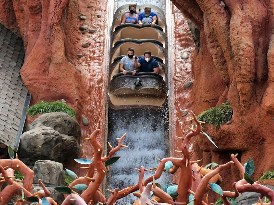 This image shows four people riding down a water attraction at Disneyland.