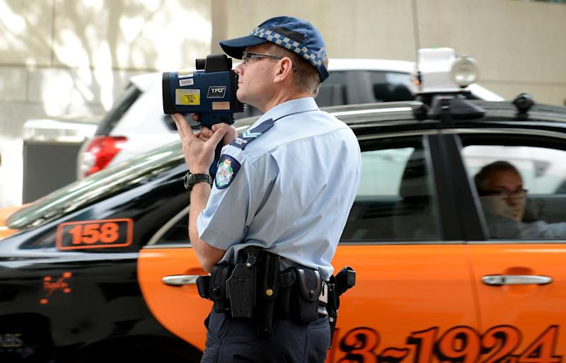 A NSW police officer with a speed gun radar. Double demerits apply in NSW, the ACT and Western Australia during the Easter long weekend.