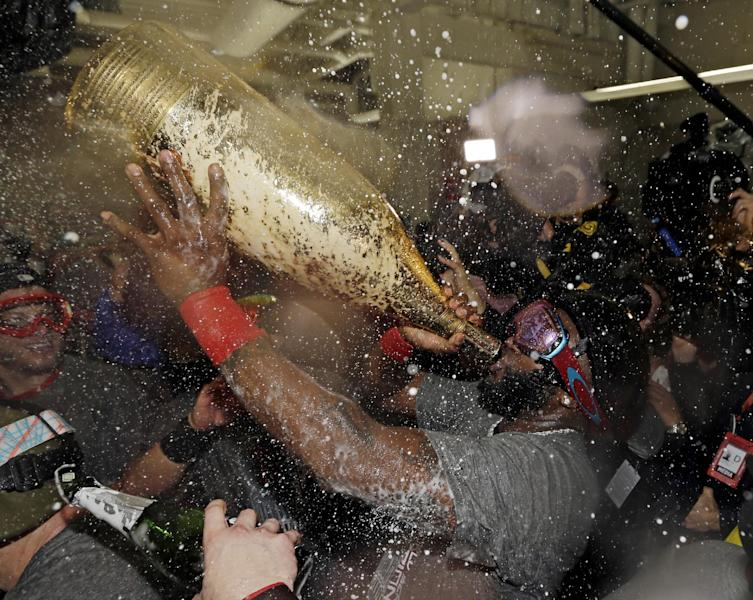 Boston Red Sox's David Ortiz drinks out of a giant bottle of Champagne as he celebrates with teammates after Game 6 of baseball's World Series against the St. Louis Cardinals Thursday, Oct. 31, 2013, in Boston. The Red Sox won 6-1 to win the series. Ortiz was names the series MVP. (AP Photo/David J. Phillip)