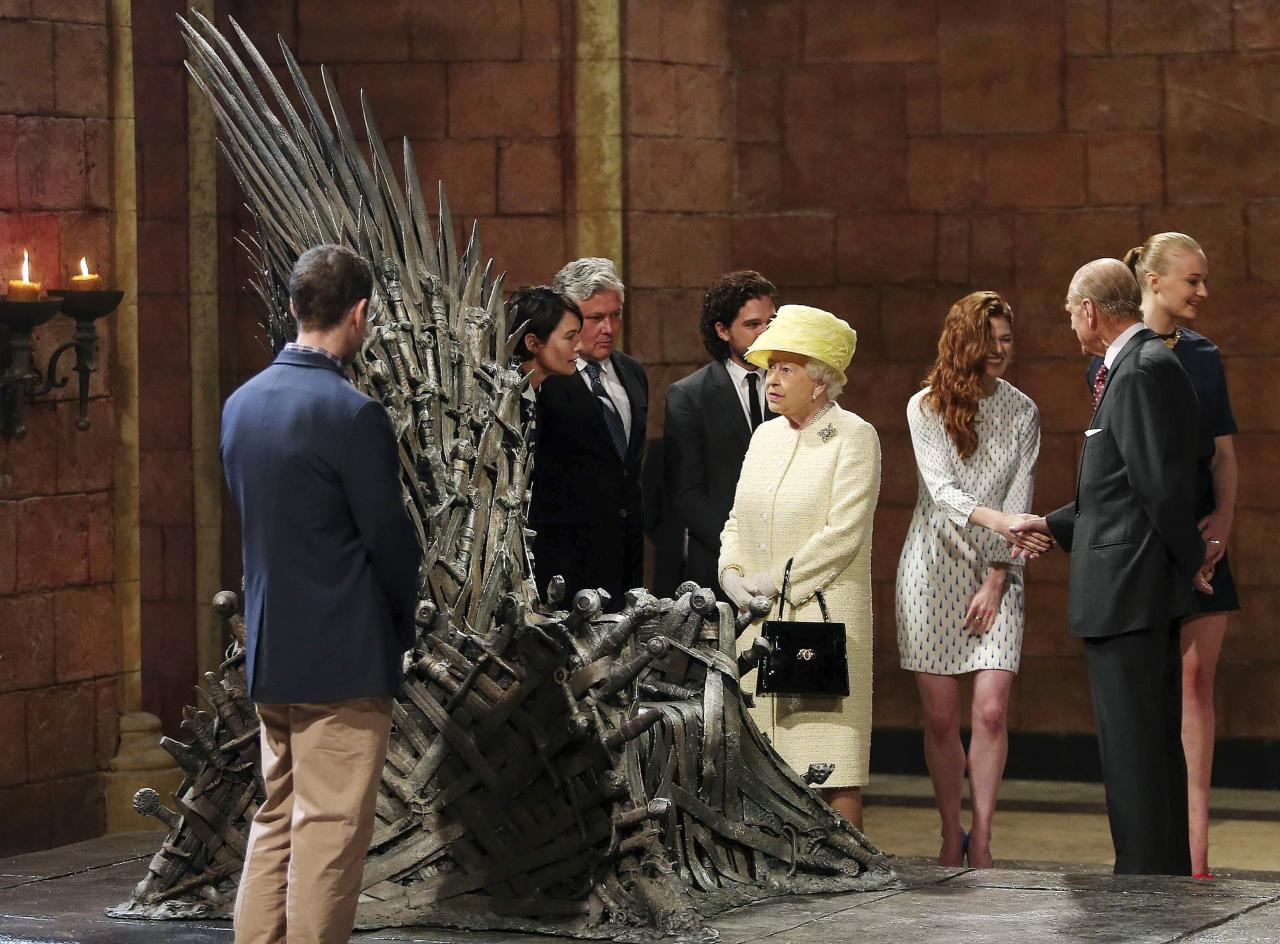 Britain's Queen Elizabeth looks at the Iron Throne as Prince Philip (2nd R) greets cast member Rose Leslie (3rd R) on the set of the television series Game of Thrones, in the Titanic Quarter of Belfast, Northern Ireland, June 24, 2014. Also pictured are Game of Thrones cast members Sophie Turner (R), Kit Harington (4th L), Conleth Hill (3rd L) and Lena Headey (2nd L). REUTERS/Jonathan Porter/Pool (NORTHERN IRELAND - Tags: ROYALS ENTERTAINMENT SOCIETY)