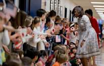 """<p>Fittingly enough, to visit Great Falls Elementary School in Great Falls, Virginia, Obama chose a floral and lace dress from Japanese-born Los Angeles-based Tadashi Shoji's <a rel=""""nofollow noopener"""" href=""""http://www.style.com/slideshows/fashion-shows/spring-2015-ready-to-wear/tadashi-shoji/collection/27"""" target=""""_blank"""" data-ylk=""""slk:Spring 2015 Ready-to-Wear collection"""" class=""""link rapid-noclick-resp"""">Spring 2015 Ready-to-Wear collection</a>. <br></p>"""