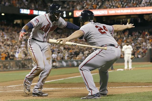 Atlanta Braves' Jason Heyward, left, is congratulated by Evan Gattis after scoring during the sixth inning of a baseball game against the San Francisco Giants in San Francisco, Tuesday, May 13, 2014. (AP Photo)