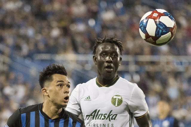 Montreal Impact's Mathieu Choiniere, left, and Portland Timbers' Modou Jadama watch the ball during the second half of an MLS soccer match in Montreal, Wednesday, June 26, 2019. (Graham Hughes/The Canadian Press via AP)
