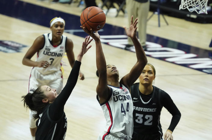 Connecticut forward Aubrey Griffin (44) shoots against Providence guard Kyra Spiwak, left, in the second half of an NCAA college basketball game at Harry A. Gampel Pavilion, Saturday, Jan. 9, 2021, in Storrs, Conn. (David Butler II/Pool Photo via AP)