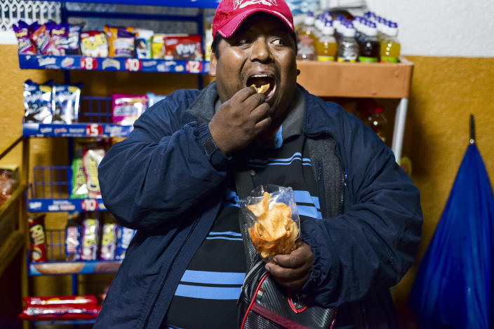 """<p>Benito Gutierréz Moreno, 40, does odd jobs in a market, including valet parking, in exchange for some pesos. He often waits all night for a car to park, and while he is waiting he drinks and eats snacks and drinks """"refrescos,"""" or sodas, which he buys in the store. He suffers from severe obesity and is not following diets or treatments to improve his health. In Mexico, 50 percent of the population lives below the poverty line, without access to quality food and with easy access to inexpensive junk food. (Photograph by Silvia Landi) </p>"""