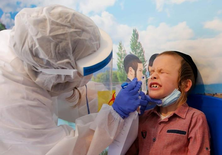 "<div class=""inline-image__caption""> <p>An Israeli medical worker takes a swab test for COVID-19 at an ultra-Orthodox Jewish school in the central Israeli city of Rechovot.</p> </div> <div class=""inline-image__credit""> Gil Cohen-Magen/AFP via Getty </div>"