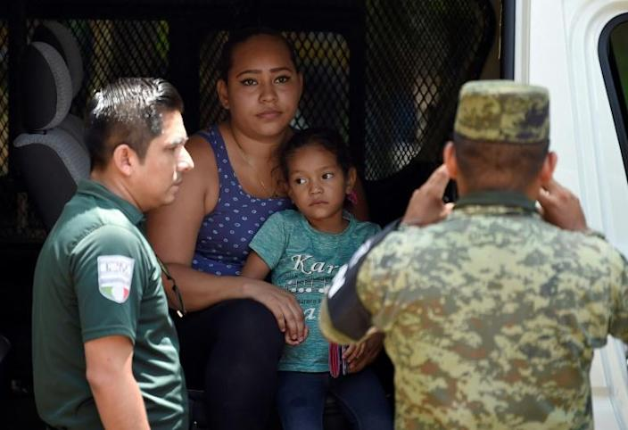 Mexican security forces detain a Nicaraguan migrant and her daughter after they crossed the Suchiate river on the border with Guatemala (AFP Photo/ALFREDO ESTRELLA)