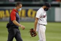 Boston Red Sox infielder Jose Peraza, right, leaves the field with a trainer after being injured while pitching during the ninth inning of a baseball game against the Tampa Bay Rays, Thursday, Aug. 13, 2020, in Boston. (AP Photo/Michael Dwyer)