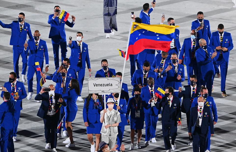 <p>Venezuela's flag bearer Karen Leon and Venezuela's flag bearer Antonio Jose Diaz Fernandez leads the delegation during the opening ceremony of the Tokyo 2020 Olympic Games, at the Olympic Stadium, in Tokyo, on July 23, 2021. (Photo by Martin BUREAU / AFP) (Photo by MARTIN BUREAU/AFP via Getty Images)</p>