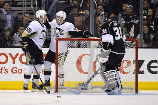 Pittsburgh Penguins left wing Tanner Glass, left, celebrates his goal with right wing Jayson Megna, center, as Los Angeles Kings goalie Martin Jones looks on during the second period of an NHL hockey game, Thursday, Jan. 30, 2014, in Los Angeles. (AP Photo)