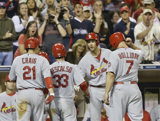 St. Louis Cardinals' Daniel Descalso is congratulated by starting pitcher Adam Wainwright as he returns to the dugout after hitting a grand slam home run against the San Diego Padres in the eighth inning of a baseball game in San Diego, Tuesday, May 21, 2013. (AP Photo/Lenny Ignelzi)
