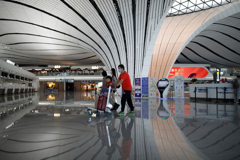 Passengers wearing face masks following the coronavirus disease (COVID-19) outbreak walk with luggages at a terminal hall of the Beijing Daxing International Airport ahead of Chinese National Day holiday, in Beijing
