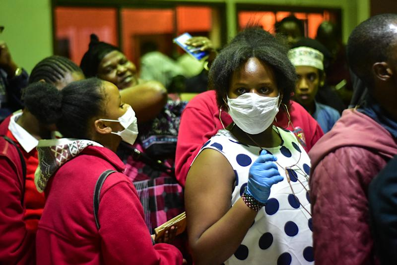 Travellers wearing face masks as protective measure wait to get their temperature checked at the border post with Kenya in Namanga, northern Tanzania, on March 16, 2020, on the day Tanzania confirmed the first case of the covid-19. - Tanzania and Somalia on March 16 became the latest East African countries to confirm their first cases of coronavirus, as neighbouring countries shuttered borders and schools as fears of contagion rose. A 46-year-old Tanzanian woman tested positive for the illness after returning from Belgium on March 15, where she had been staying with a relative sick with coronavirus. (Photo by Filbert RWEYEMAMU / AFP) (Photo by FILBERT RWEYEMAMU/AFP via Getty Images)
