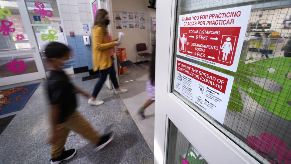 Students walk past a social distancing reminder sign while heading to the nurse's office to be tested for COVID-19, during summer school at the E.N. White School in Holyoke, Mass., on Wednesday, Aug. 4, 2021. Schools across the U.S. are about to start a new year amid a flood of federal money larger than they've ever seen before, an infusion of pandemic relief aid that is four times the amount the U.S. Department of Education sends to K-12 schools in a typical year. (AP Photo/Charles Krupa)