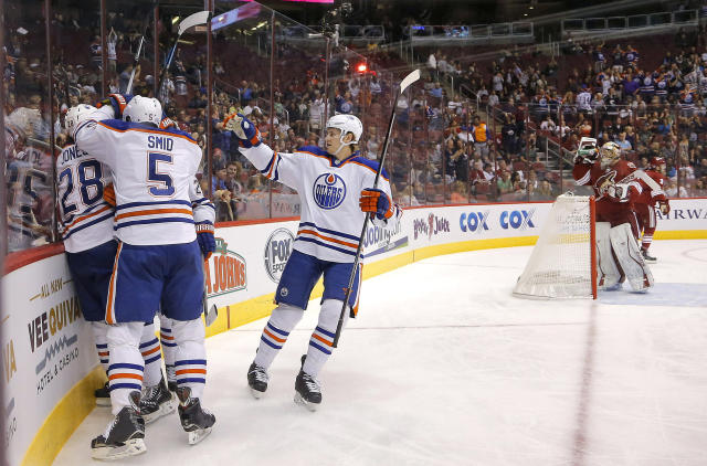 Edmonton Oilers' Smid Ladislav (5), of Czech Republic, Ryan Jones (28) and Jeff Petry celebrate a goal by teammate Tyler Pitlik with Phoenix Coyotes goalie Mike Smith at right during the first period of an NHL hockey game, Saturday, Oct. 26, 2013, in Glendale, Ariz. (AP Photo/Matt York)