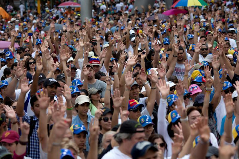 Demonstrators raise their arms in solidarity during a rally with human rights activists, in Caracas, Venezuela, Friday, Feb. 28, 2014. The start of a weeklong string of holidays leading up to the March 5 anniversary of former President Hugo Chavez's death has not completely pulled demonstrators from the streets as the government apparently hoped. President Nicolas Maduro announced this week that he was adding Thursday and Friday to the already scheduled long Carnival weekend that includes Monday and Tuesday off, and many people interpreted it as an attempt to calm tensions. (AP Photo/Rodrigo Abd)